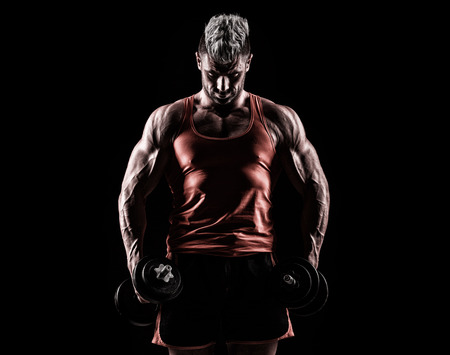 powerfully: handsome young man in the studio with dumbbells on a dark background