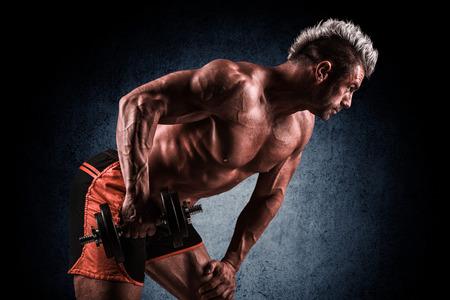 salud sexual: apuesto joven que hace ejercicios con pesas en un fondo oscuro