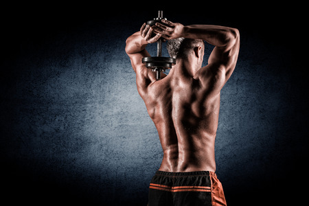 gym: strong and handsome young man doing exercise with dumbbells Stock Photo