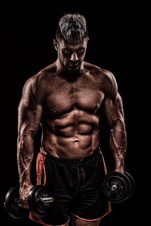 powerfully: young handsome man doing exercise with dumbbells in studio on dark background Stock Photo