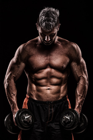 young handsome man doing exercise with dumbbells in studio on dark background Stock Photo