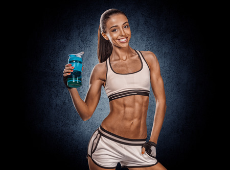 beautiful young athletic girl with a bottle on a dark background photo