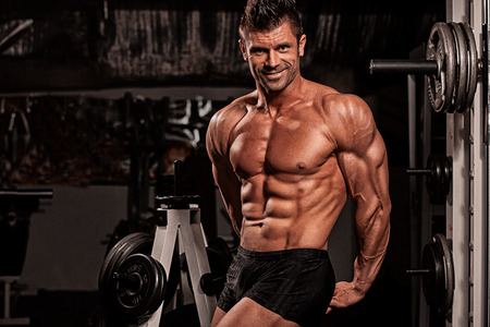 male body: dark background is engaged in fitness Stock Photo
