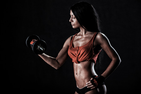 beautiful woman on a dark background is engaged in fitness photo