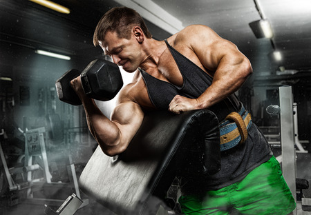 execute exercise with dumbbells, on bkack background. Stock Photo