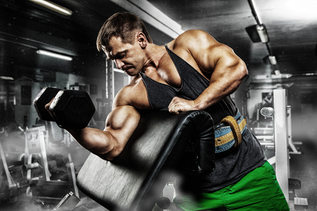 musculation: very power athletic guy bodybuilder , execute exercise with dumbbells