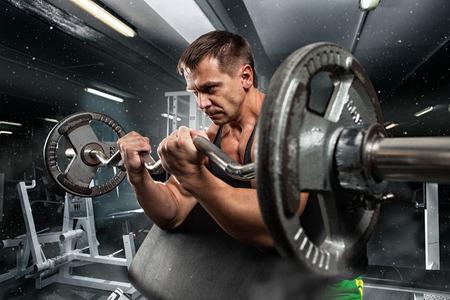 健身: 英俊的男子與大肌肉群,在相機在健身房冒充