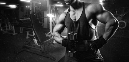 only the biceps: young man doing heavy weight exercise for biceps