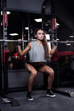 en cuclillas: Beautiful brunette during workout in gym