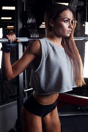 en cuclillas: Hermosa morena durante entrenamiento en gimnasia