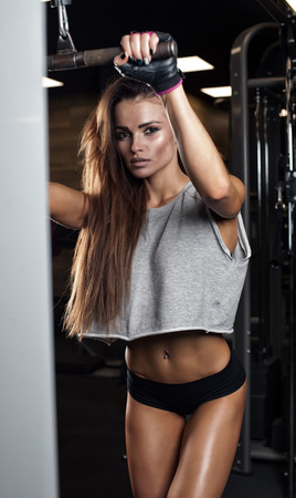 only the biceps: Brunette sexy fitness girl in sport wear with perfect body in the gym posing before training set