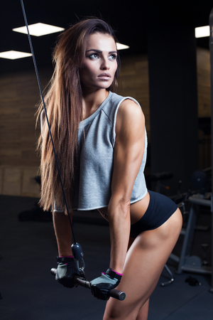 only the biceps: beautiful girl bodybuilder , execute exercise with dumbbells, in dark gym Stock Photo