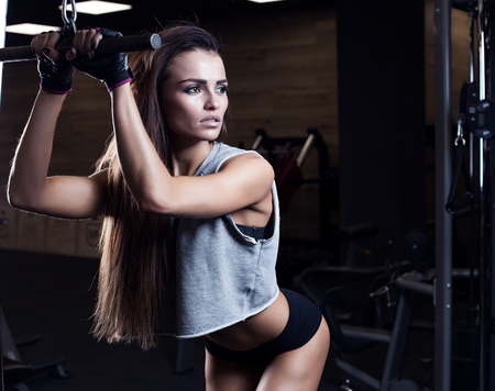 face female: beautiful girl bodybuilder , execute exercise with dumbbells, in dark gym Stock Photo