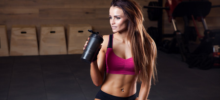 Fitness girl with shaker relaxing in the gym