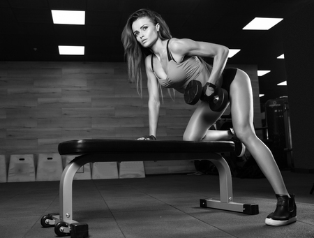 woman muscle: Beautiful brunette during workout in gym