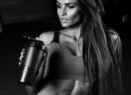 tomando agua: Deportivo musculoso conjunto mujer agua potable foto de deportivo musculoso chica morena femenina