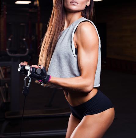 abdomen plano: hermosa chica culturista, ejecutar el ejercicio con pesas, en el gimnasio oscura Foto de archivo