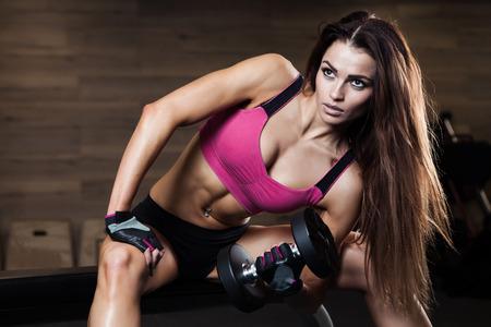Jonge atletische vrouw die haar biceps met zware halters Stockfoto