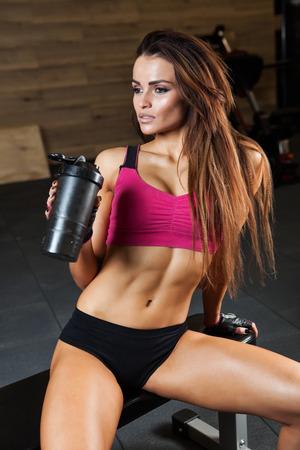 haciendo ejercicio: Deportivo musculoso mujer beber agua foto conjunto de deportivo musculoso mujer morena chica Foto de archivo