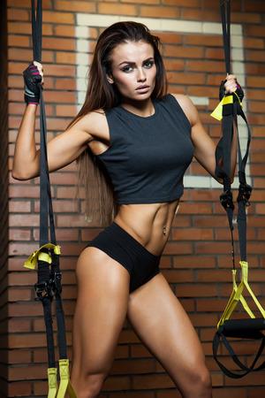 forme et sante: Athletic jeune femme brune en tenue de sport gris, des trains sur les anneaux dans le gymnase Banque d'images