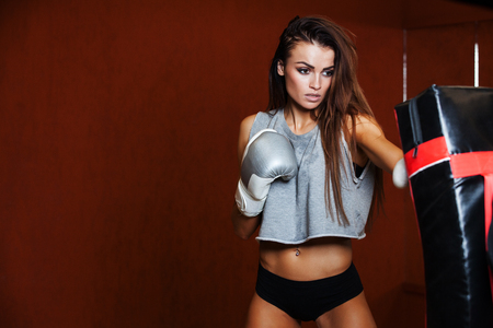 women sport: punching bag, on the background wall of red brick.