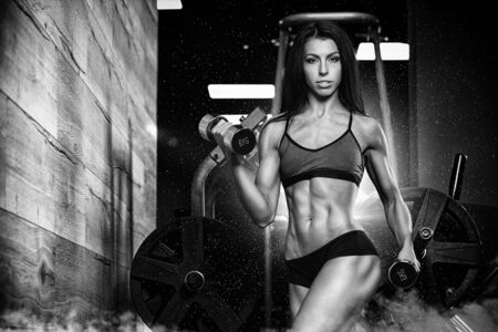 sport fitness: Brunette fitness woman in black sport wear with perfect fitness body