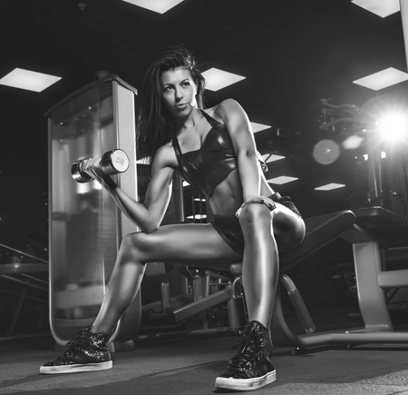 female fitness: beautiful woman on a dark background is engaged in fitness Stock Photo