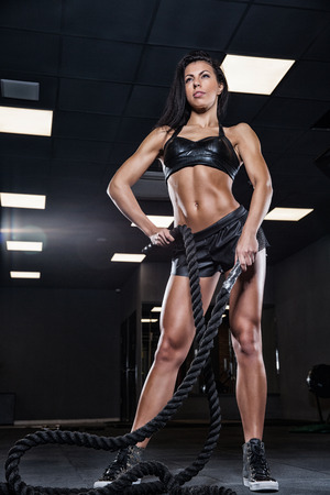 only the biceps: Young woman training in the dark gym