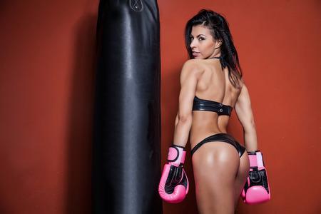 sexy girl punching boxing bag
