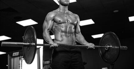 only the biceps: handsome bodybuilder works out pushing up excercise in gym