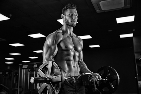 excercise: handsome bodybuilder works out pushing up excercise in gym
