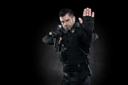 spec: Spec ops police officer SWAT in black uniform studio