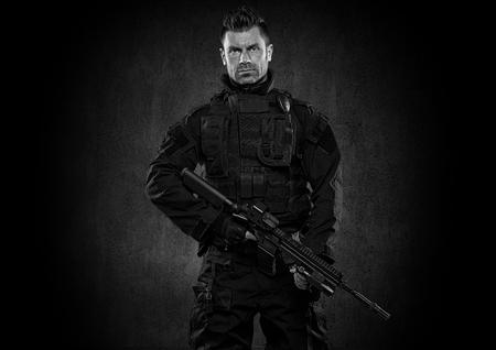 counter terrorism: Spec ops police officer SWAT in black uniform studio