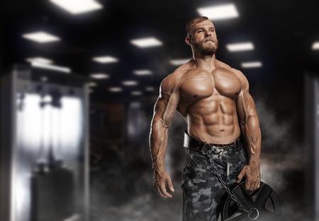 Muscoloso atletico bodybuilder modello in posa dopo esercizi in palestra Archivio Fotografico - 62137280