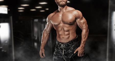 musculoso: Atlética muscular del gimnasio culturista modelo posando después de ejercicios en el gimnasio Foto de archivo
