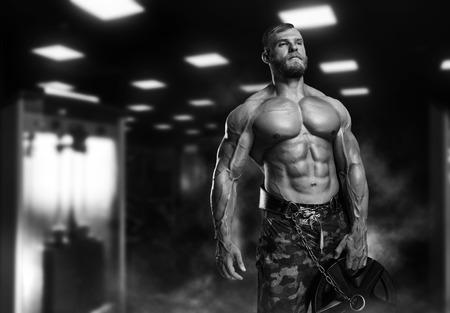 Muskulöser athletischer Bodybuilder Fitness-Modell posiert nach Übungen im Fitness-Studio