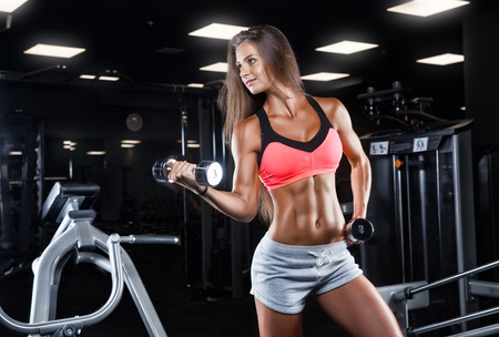 attractive young woman working out with dumbbells - bikini fitness girl