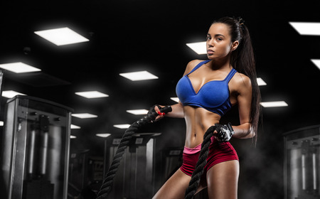 musculation: Sexy girl is training with rope  in the gym