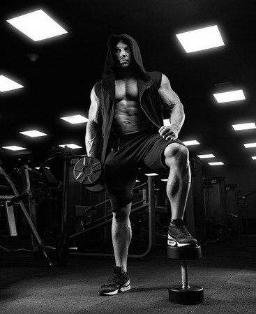musculation: adult bodybuilder doing weight lifting in gym.
