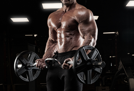 man working out: Muscular man working out in gym doing exercises with dumbbells