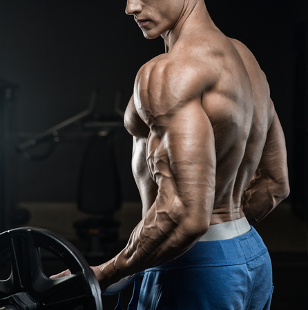 sportsmen: Handsome man with big muscles, posing at the camera in the gym