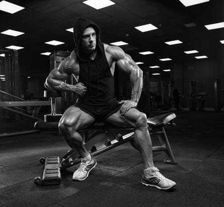 Hombre guapo con grandes músculos, posando en la cámara en el gimnasio