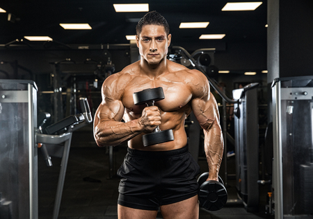execute: Very power athletic guy bodybuilder, execute exercise with dumbbells