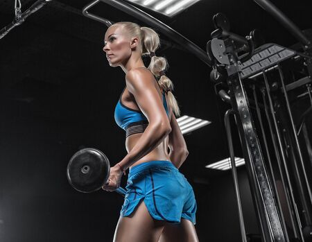 Brunette sexy fitness girl in blue sport wear with perfect body in the gym posing before training set Stock Photo