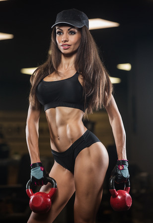 Fitness woman posing in the gym. Perfect physique athletic young woman with six pack, perfect abs, shoulders and biceps. Crossfit woman Stock Photo