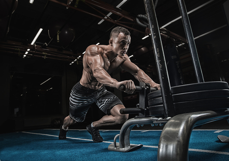 sled push man pushing weights workout exercise at gym Stock Photo