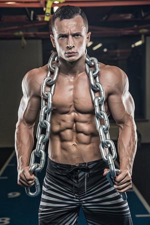 Bodybuilder adultos jóvenes haciendo levantamiento de pesas en el gimnasio.