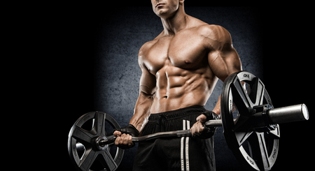 strong and handsome young man doing exercise with dumbbells Imagens