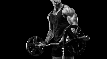 strong and handsome young man doing exercise with dumbbells Stock Photo