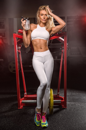 Young beautiful sexy young blond woman, in sportswear, at the gym drinking sports nutrition. Stock Photo